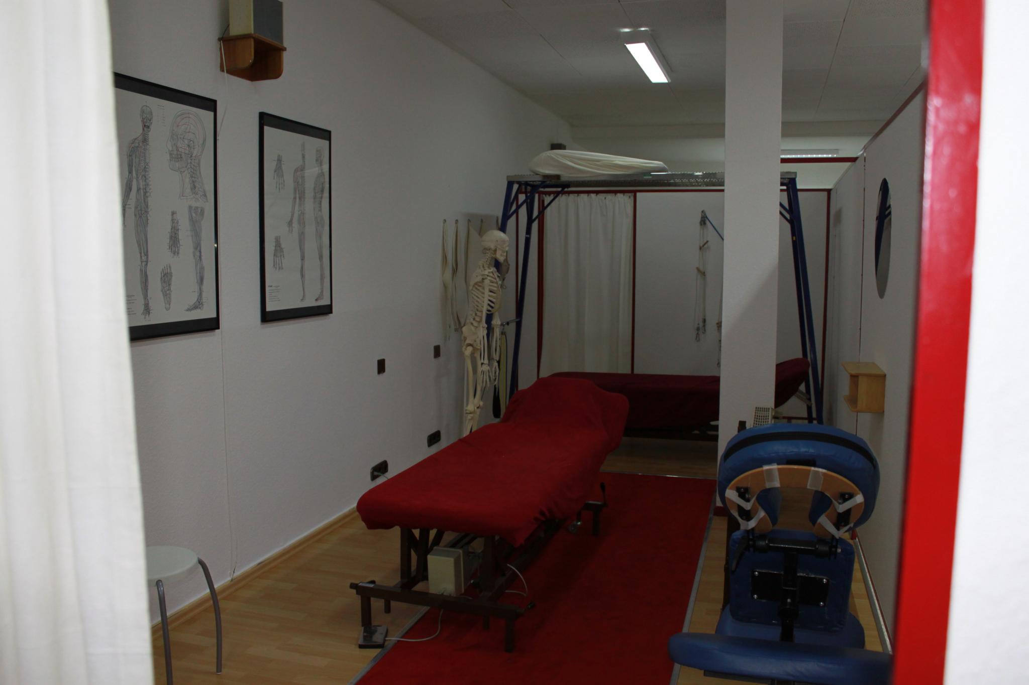 Das Bild zeigt einen Behandlungsraum. Im Zentrum sehen Sie eine Liege mit rotem Stoffbezug. Rechts vorne steht ein blauer Stuhl, auf dem die Therapeuten zur Entlastung bei der Arbeit Platz nehmen können. Links neben der Liege steht in Höhe des Kopfteils ein Vollkörpersketett. An der Wand hängen zwei schematische Abbildungen, die Muskel- und Nervengewebe und Blutkreislauf des menschlichen Gesamtkörpers und Körperteile wie Füße und Hände oder Kopf darstellen. In hinteren Bereich steht ein sogenannter Schlingentisch.
