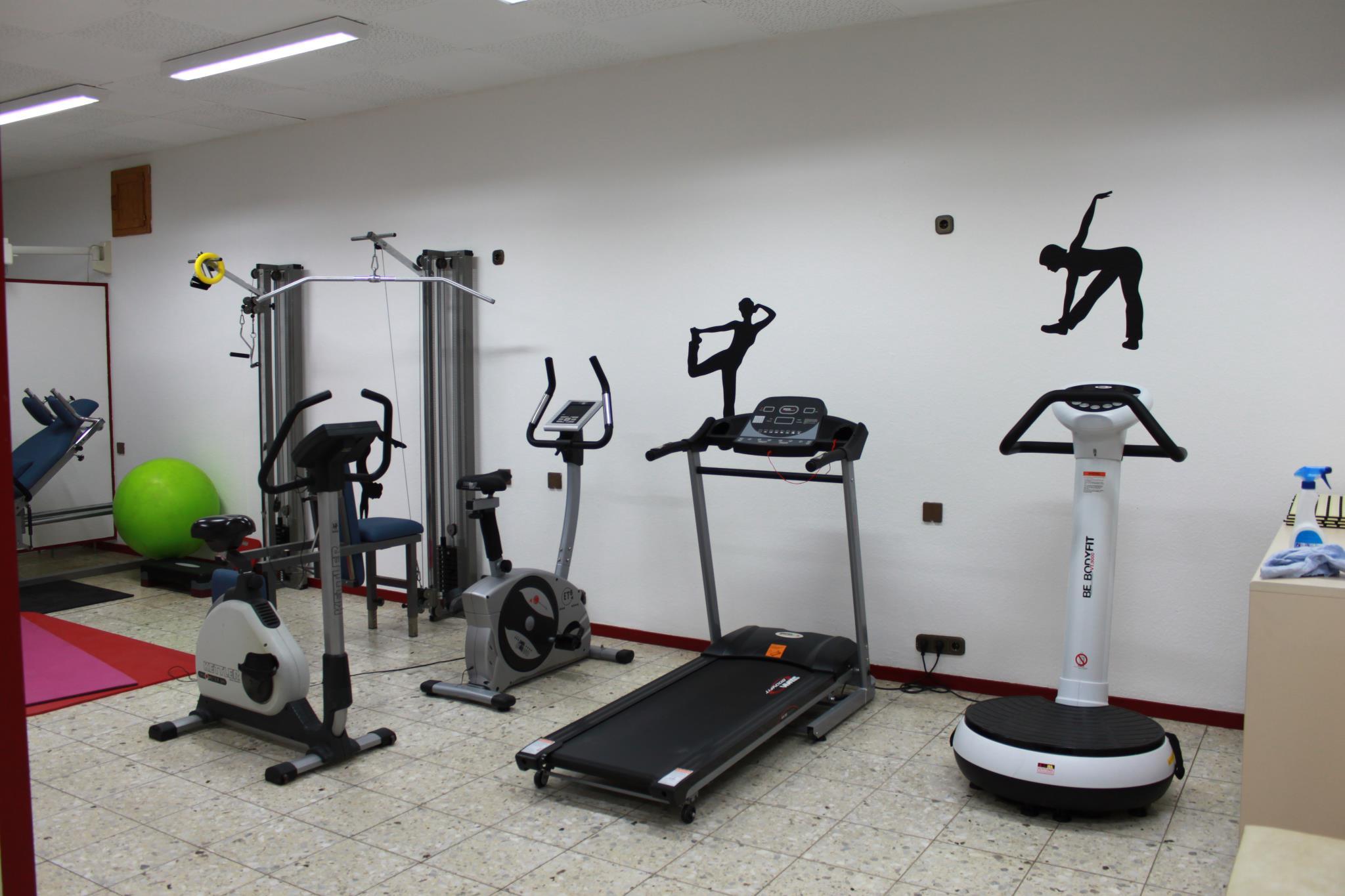 Das Bild stellt verschiedene Trainingsgeräte dar. Von links nach rechts: rote und lila Gymnastikmatten, eine Beinpresse, ein grüner Pezziball, zwei Zugapparate, ein Ergoh-Mehter (Trimmrad), ein Laufband und eine Vibrationsplatte. An der dem Betrachter zugewandten Wandfläche sind zwei schwarze weibliche Silhouetten zu sehen, die Gymnastik betreiben.